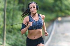 Giovane donna di forma fisica che pareggia nel parco Immagini Stock