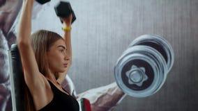 Giovane donna di forma fisica che si esercita nella palestra con le teste di legno archivi video
