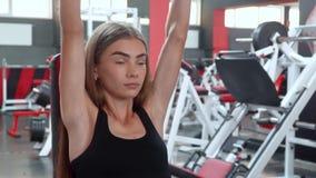 Giovane donna di forma fisica che si esercita nella palestra con le teste di legno che si siedono sul banco stock footage