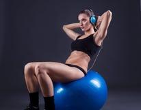 Giovane donna di forma fisica che si siede sulla palla, su fondo nero Immagini Stock Libere da Diritti
