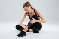 Giovane donna di forma fisica che soffre da un dolore della caviglia Fotografia Stock