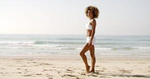 Giovane donna di forma fisica che sta sulla spiaggia stock footage