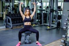 Giovane donna di forma fisica che tiene un peso della mano Fotografia Stock