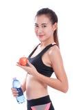 Giovane donna di forma fisica che tiene una bottiglia di acqua e di una mela fotografie stock libere da diritti
