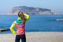 Giovane donna di forma fisica ed in buona salute di stile di vita che sta sulla spiaggia nel g immagini stock