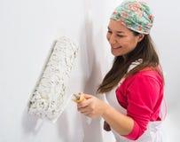 Giovane donna di Hapy che dipinge una parete immagine stock libera da diritti