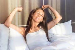 Giovane donna di mattina che sveglia allungandola armi che si trovano a letto immagine stock libera da diritti