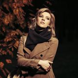 Giovane donna di modo in cappotto beige che cammina nel parco della città di autunno alla notte fotografie stock libere da diritti