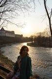 Giovane donna di modo che si rilassa e che gode del tramonto vicino ad un fiume in Bauska, Lettonia, 2019 immagine stock