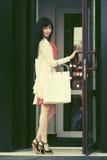 Giovane donna di modo con i sacchetti della spesa alla entrata del centro commerciale fotografia stock libera da diritti