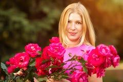 Giovane donna di modo della molla con le rose nel giardino di primavera springti Fotografie Stock Libere da Diritti