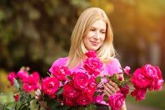 Giovane donna di modo della molla con le rose nel giardino di primavera springti Fotografia Stock