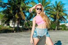 Giovane donna di modo e bella che posa con un pattino vicino alle palme Fotografie Stock Libere da Diritti