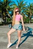 Giovane donna di modo e bella che posa con un pattino vicino alle palme Fotografia Stock Libera da Diritti