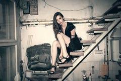 Giovane donna di modo in poco vestito nero nel vecchio studio s dell'artista fotografia stock libera da diritti