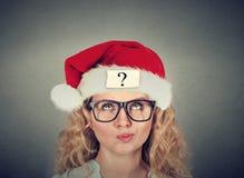 Giovane donna di pensiero in cappello del Babbo Natale con il punto interrogativo Fotografie Stock Libere da Diritti