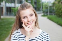 Giovane donna di pensiero in una camicia a strisce Fotografia Stock