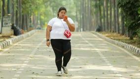 Giovane donna di peso eccessivo che cammina al parco archivi video
