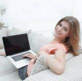 Giovane donna di Portret che lavora con il computer portatile che si siede sul sofà Fotografia Stock Libera da Diritti