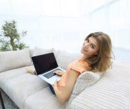 Giovane donna di Portret che lavora con il computer portatile che si siede sul sofà Immagine Stock
