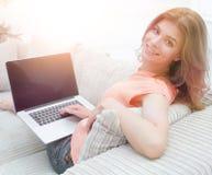 Giovane donna di Portret che lavora con il computer portatile che si siede sul sofà Immagine Stock Libera da Diritti