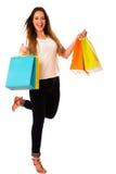 Giovane donna di Preety con i sacchetti della spesa variopinti isolati sopra il whi Immagini Stock