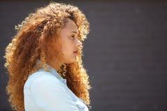 Giovane donna di profilo con capelli ricci contro la parete grigia fotografia stock
