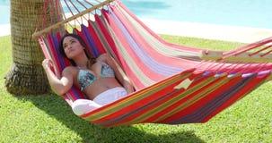 Giovane donna di rilassamento in amaca variopinta stock footage