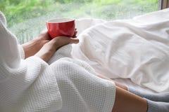 Giovane donna di rilassamento che gode del suo caffè mentre sedendosi a letto immagini stock