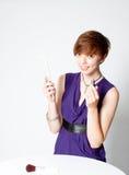 Giovane donna di risata che applica rossetto fotografia stock