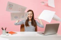 Giovane donna di risata che getta sui documenti cartacei mentre lavorando al progetto, sedentesi all'ufficio con il computer port fotografia stock