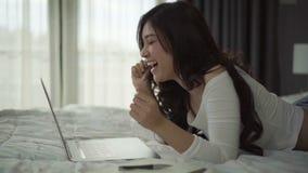 Giovane donna di risata che si trova a letto e per mezzo del computer portatile stock footage