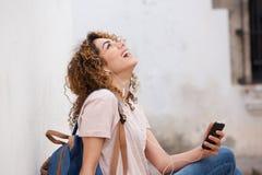 Giovane donna di risata con il telefono cellulare e le cuffie Fotografia Stock
