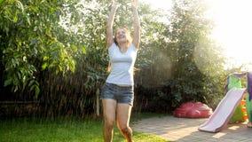 Giovane donna di risata felice che balla sotto la pioggia al giardino Ragazza che gioca e che si diverte all'aperto all'estate fotografia stock