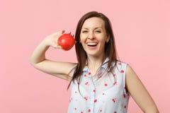 Giovane donna di risata in vestiti di estate che giudicano la frutta rossa matura fresca della mela isolata sul fondo pastello ro fotografie stock