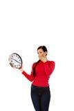 Giovane donna di sbadiglio che tiene un orologio Fotografie Stock