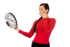 Giovane donna di sbadiglio che tiene un orologio Fotografia Stock