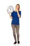Giovane donna di sbadiglio che tiene un orologio Fotografie Stock Libere da Diritti