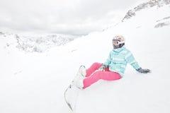 Giovane donna di seduta con lo snowboard Fotografia Stock Libera da Diritti