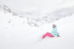 Giovane donna di seduta con lo snowboard Immagine Stock