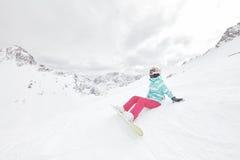 Giovane donna di seduta con lo snowboard Immagini Stock