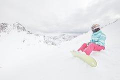 Giovane donna di seduta con lo snowboard Fotografie Stock