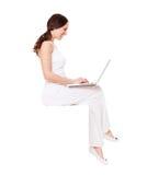 Giovane donna di smiley che si siede con il computer portatile Fotografia Stock Libera da Diritti