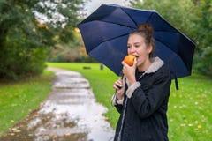 Giovane donna di Smilling che mangia mela all'aperto immagini stock libere da diritti