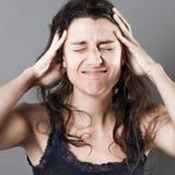 Giovane donna di sofferenza con le mani in suoi capelli che hanno emicrania Fotografia Stock Libera da Diritti