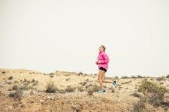 Giovane donna di sport che cola la strada sporca della traccia della strada con il fondo asciutto del paesaggio del deserto che s Immagine Stock Libera da Diritti