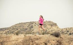 Giovane donna di sport che cola la strada sporca della traccia della strada con il fondo asciutto del paesaggio del deserto che s Immagini Stock
