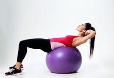 Giovane donna di sport che fa allenamento dell'ABS su fitball Fotografie Stock Libere da Diritti