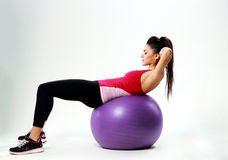 Giovane donna di sport che fa allenamento dell'ABS su fitball Immagini Stock
