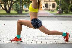 Giovane donna di sport che fa gli esercizi durante l'addestramento fuori nel parco della città All'aperto corrente di modello di  Immagini Stock Libere da Diritti